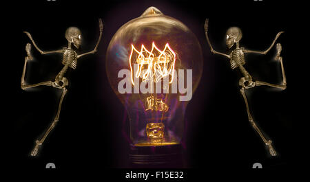 Scary vintage Halloween themed skeletons gesturing towards Edison lightbulb - Stock Photo