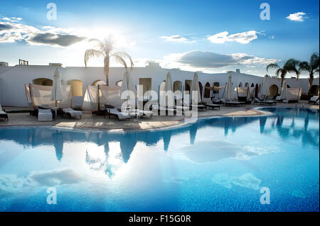 Swimming pool in hotel at the sunrise - Stock Photo