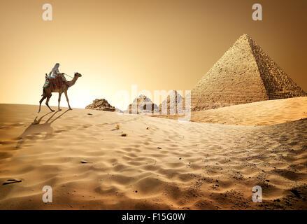 Bedouin on camel near pyramids in desert - Stock Photo