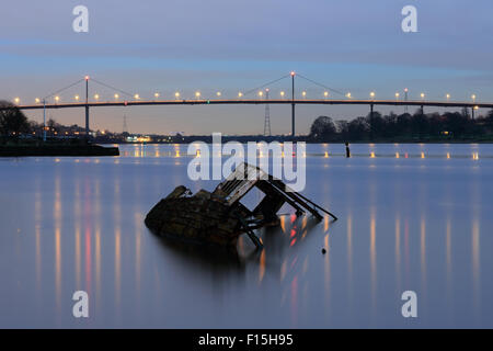 Shipwreck by Bowling Harbour with Erskine Bridge in the background at Sunset - Stock Photo