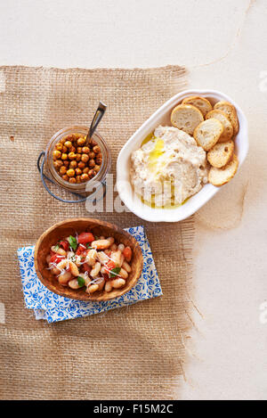 Three bean side dishes, kidney beans, hummus and chick peas in bowls on burlap, studio shot - Stock Photo