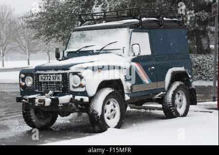 Blue Land Rover Defender 90 (rugged 4x4 vehicle) partly covered in white snow, parked at the roadside on a snowy - Stock Photo
