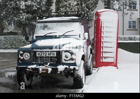 Two British icons covered in white snow - Land Rover Defender 90 parked alongside a red English phone box on a snowy - Stock Photo