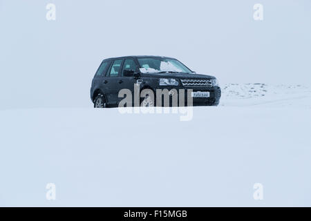 Black 4x4 set against white snowy background - Land Rover Freelander 2 four-wheel drive vehicle parked in the snow - Stock Photo