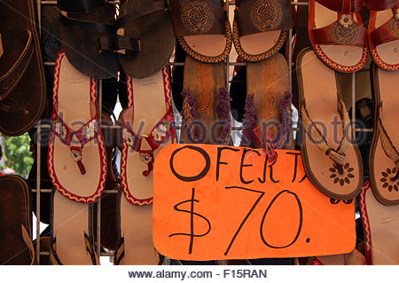 Closeup street shot Mexico display of hand made leather sandals with sign in Spanish showing price bright sunny - Stock Photo