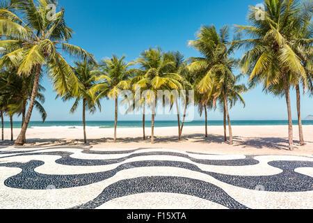 Palm trees and the iconic Copacabana beach mosaic sidewalk, in Rio de Janeiro, Brazil. - Stock Photo