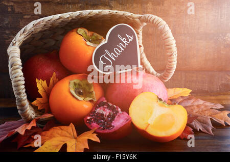Thanksgiving Autumn feast fruit, with persimmons and pomegranates tumbling out of a basket with Thanks message on - Stock Photo