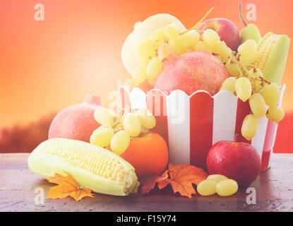 Bowl of Autumn fruit and vegetables on vintage wood table with Autumn sunset background, with added filters and - Stock Photo