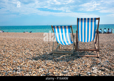Two deck chairs on the beach facing sea, Brighton, UK