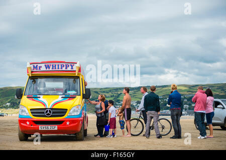 People queueing to buy soft Mr Whippy icecream  from a van on the beach at Ynyslas Wales UK - Stock Photo