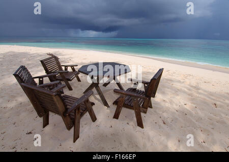 Oct. 15, 2014 - Seychelles - Four wooden chairs and a table stand on the sandy shores of the Indian Ocean, Denis - Stock Photo