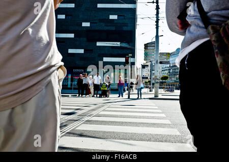 people waiting at the pedestrian crossing, viewed from behind the back of other people - Stock Photo