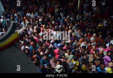Malang, Indonesia. 28th Aug, 2015. People queue up to get foodstuff during the Hungry Ghost Festival almsgiving - Stock Photo
