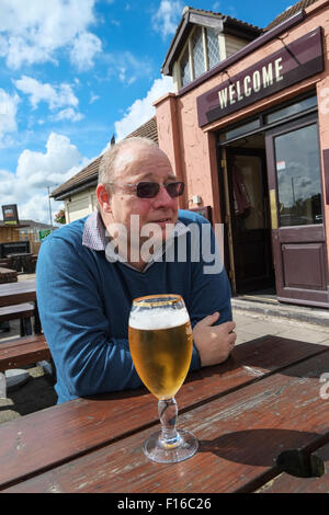 Middle-aged man sat outside a pub drinking a pint of lager with Welcome sign in background - Stock Photo