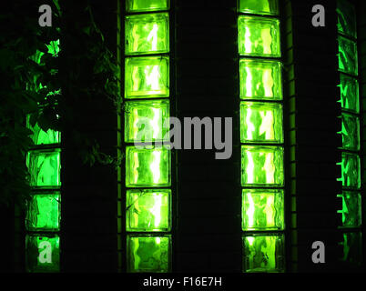 Decorative wall with green glowing at night with the vertical glass panels for use as background or wallpaper - Stock Photo