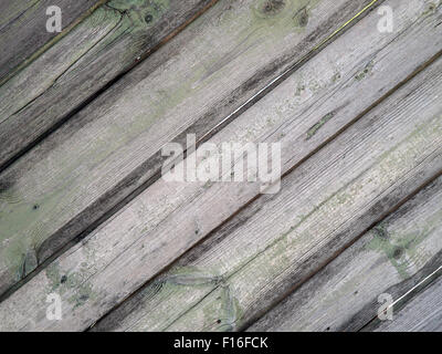 Detail of an old  gray wooden fence with the remains of green paint on the mangy dark boards with cracks for use - Stock Photo
