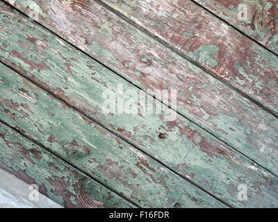 Detail of an old  diagonal wooden fence with the remains of green paint on the mangy dark boards with cracks for - Stock Photo