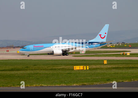 Thomson Airways Boeing 737 passenger plane taxiing on Manchester Airport runway. - Stock Photo
