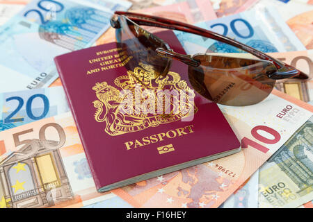 Travel things with a British passport Euro currency and sunglasses for travelling to Eurozone countries from UK. - Stock Photo