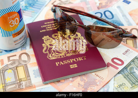 Travel things with British biometric passport Euro currency suncream and sunglasses for travelling to Eurozone countries - Stock Photo