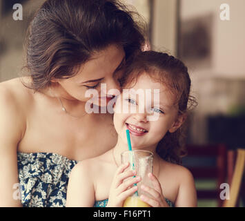Happy mother looking and hugging her daughter who drinking citrus juice and smiling in restaurant. Closeup portrait - Stock Photo