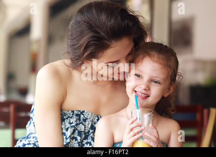 Happy mother looking and hugging her daughter who drinking citrus juice in urban restaurant - Stock Photo