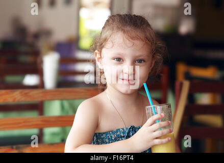 Happy smiling kid girl drinking fresh juice from glass in cafe - Stock Photo