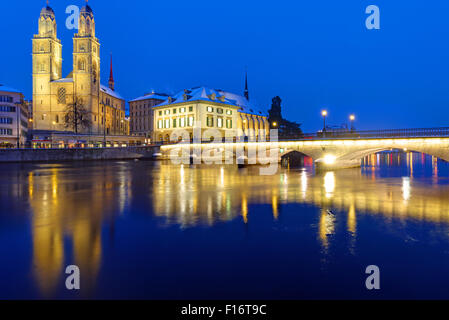 A bridge and the Minster in Zurich in winter at night - Stock Photo