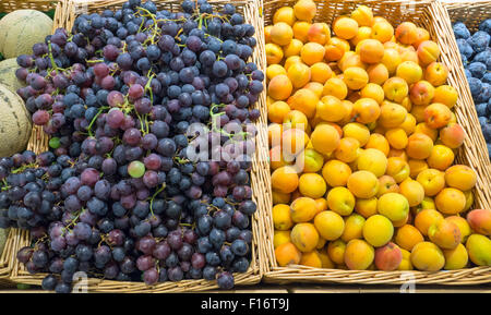 Grapes and yellow plums for sale on a market - Stock Photo
