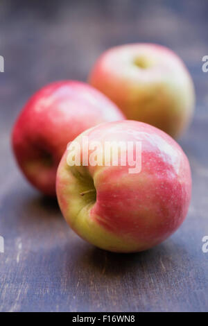 Malus domestics. Three eating apples on a wooden table. - Stock Photo