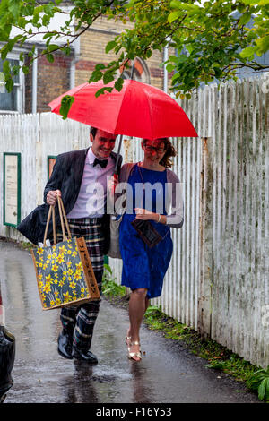 Young Opera Fans Arrive In The Pouring Rain At Lewes Station En Route To Glyndebourne Opera House, Lewes, Sussex, - Stock Photo