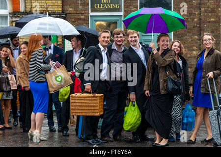 Young Opera Fans Wait In The Pouring Rain At Lewes Station For A Bus Take Them To Glyndebourne Opera House, Lewes, - Stock Photo