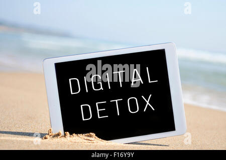 a tablet computer with the text digital detox written in its screen, placed in the sand of a beach - Stock Photo