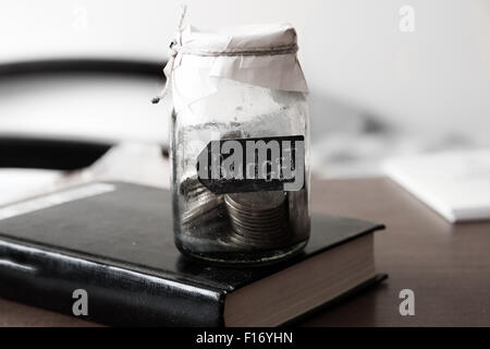 Budget concept. Glass bank with many world coins and budget word or label on saving money jar, toned. - Stock Photo