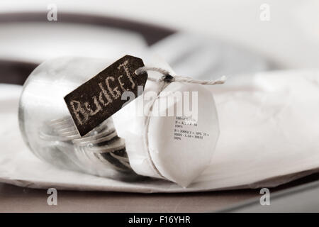 Glass bank with many world coins and budget word or label on saving money jar, chalk inscription - Stock Photo