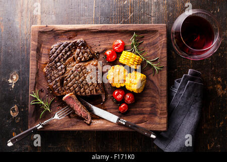 Sliced Medium rare grilled Steak Ribeye Black Angus with corn and cherry tomatoes on serving board block on wooden - Stock Photo