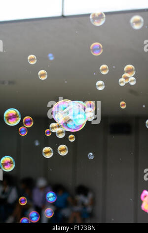 Bubbles floating in air lots of colors depth of field - Stock Photo