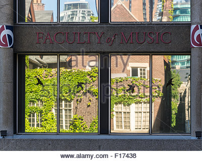 New vs Old: Vintage building reflected in the windows of the Faculty of Music block at the University of Toronto. - Stock Photo