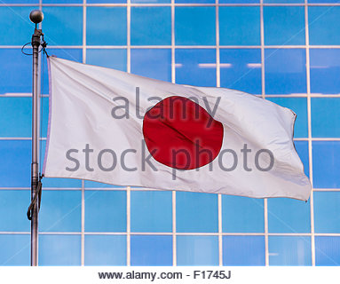 Japanese Flag In Wind Against Clear Blue Sky Stock Photo