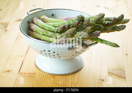 Fresh green asparagus in a white enamel colander on a rustic wooden table - Stock Photo