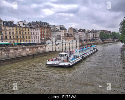 Paris, France, Europe - June 21, 2013: tourist boat (Bateaux-Mouches) with passengers on board cruising along the - Stock Photo