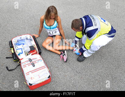 A Paramedic helping a female runner wiht ankle accident - Stock Photo