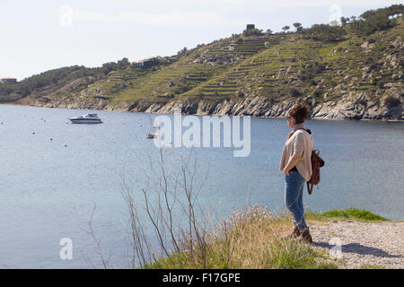 Woman standing and looking to the sea, in the seashore - Stock Photo