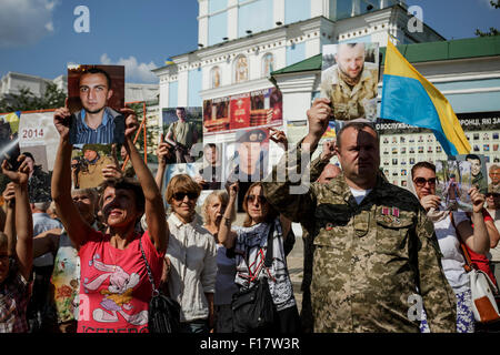 People hold portraits of Ukrainian servicemen killed during the 2014 battle which took place in a small town near - Stock Photo