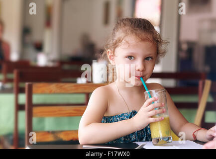 Cute small kid girl drinking juice in cafe with serious look - Stock Photo