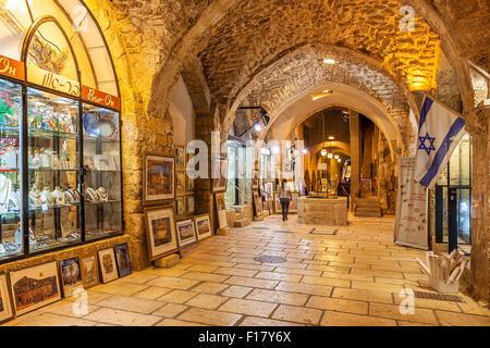 Gift shops  gallery in ancient stone vault passage in Old City of Jerusalem, Israel. - Stock Photo