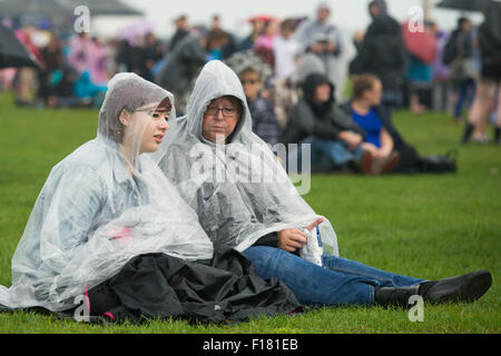 Portsmouth, UK. 29th August 2015. Victorious Festival - Saturday. Two women sit on the grass in ponchos protecting - Stock Photo