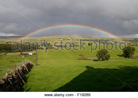 Holwick, Middleton-in-Teesdale, Co Durham UK. The summer sun breaks through the dark skies to give a dramatic rainbow - Stock Photo