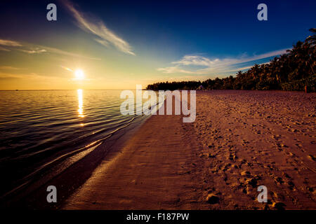 Footprints on the tropical beach at sunset with sun over ocean - Stock Photo