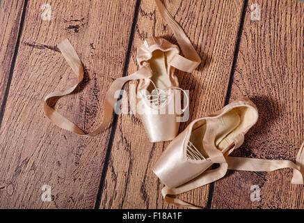 Ballet pointe shoes lie on the wooden floor. Vintage. The concept of classical ballet and contemporary dance. Shot - Stock Photo
